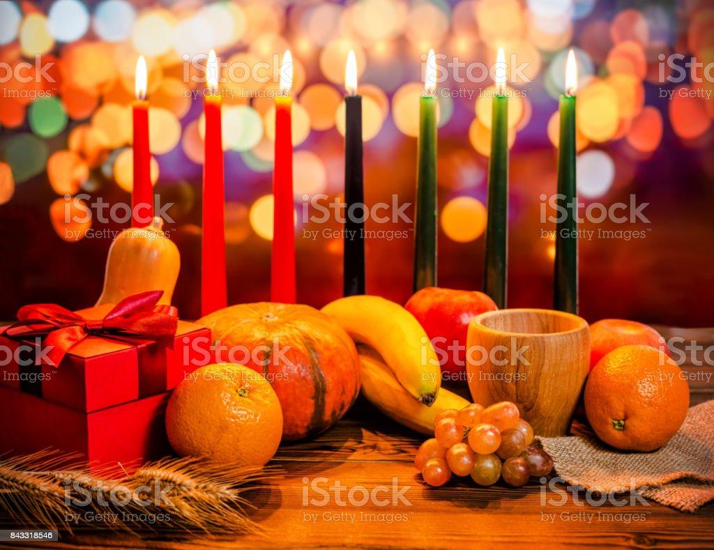 Concepto de día de fiesta de Kwanzaa con decorar siete velas rojo, negro y verde, caja de regalo, calabaza, tazón de fuente y fruto de luz desenfocar fondo bokeh - foto de stock