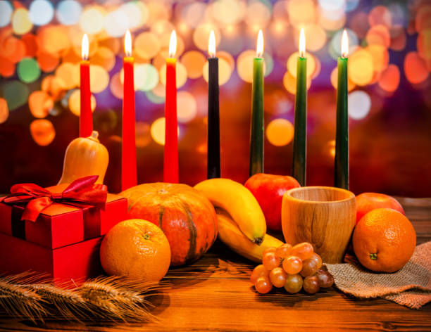Concept de vacances de Kwanzaa avec décorer vert, noir et rouge de sept chandelles, coffret cadeau, citrouille, bol et fruits sur lumière flou fond de bokeh - Photo
