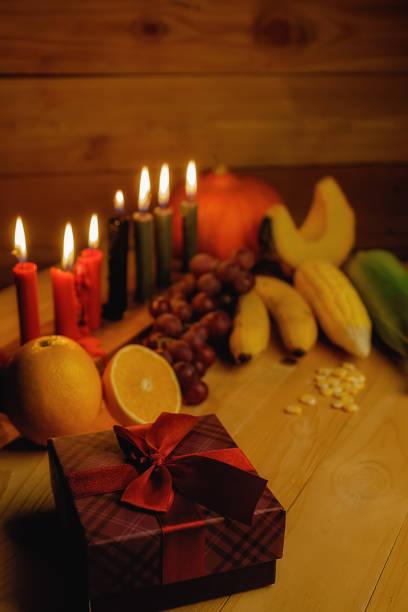 Concept de vacances de Kwanzaa avec décorer sept bougies rouges, noirs et verts, coffret cadeau, potiron, maïs et fruits sur bureau en bois et fond. - Photo