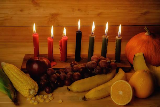 クワンザ休日の概念は、7 キャンドル赤、黒、緑、ギフト ボックス、カボチャ、トウモロコシ、木製の机と背景にフルーツを飾る。 - クワンザ ストックフォトと画像