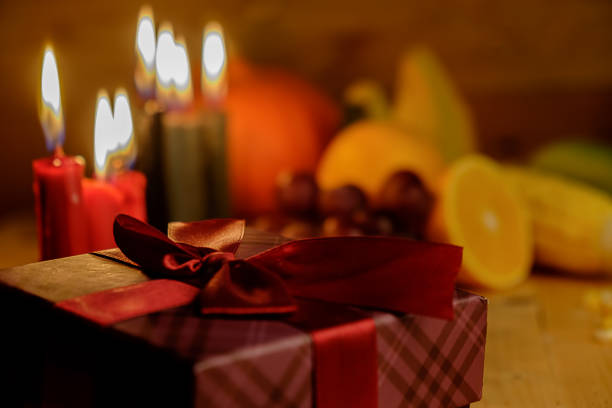 kwanzaa holiday concept with decorate seven candles red, black and green, gift box, pumpkin,corn and fruit on wooden desk and background. - kwanzaa stock pictures, royalty-free photos & images