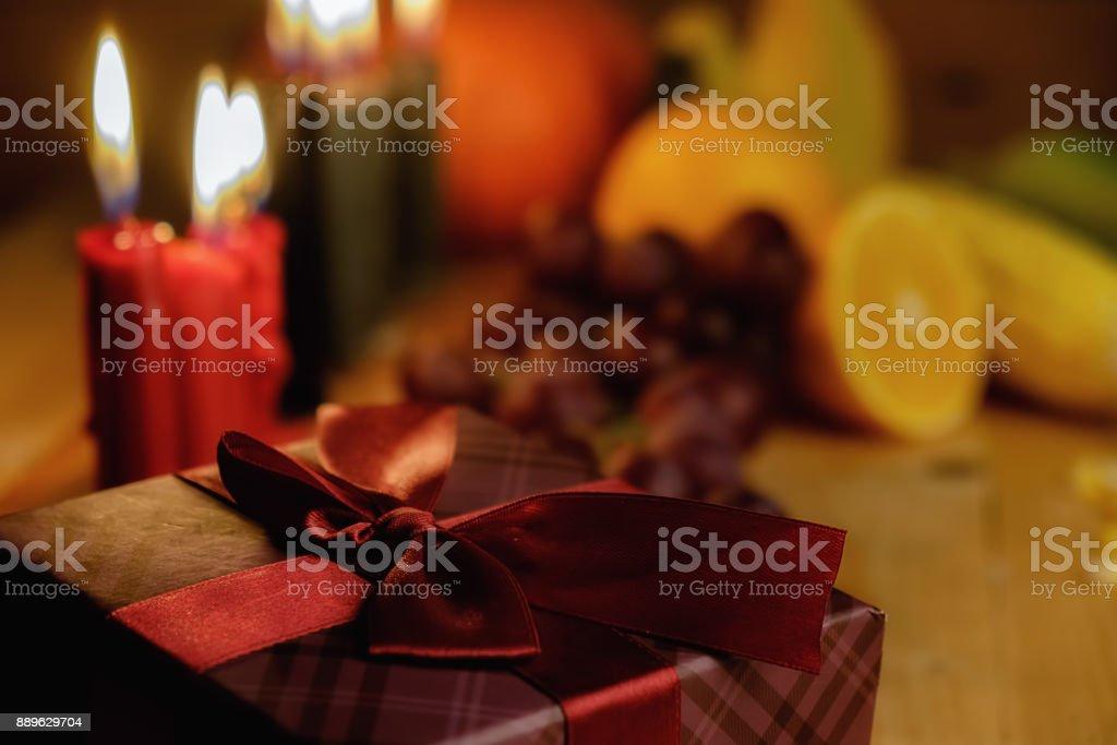 Concepto de día de fiesta de Kwanzaa con decorar siete velas rojos, negros y verdes, caja de regalo, calabaza, maíz y frutas en el mostrador de madera y fondo. - foto de stock