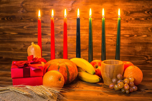 kwanzaa holiday concept with traditional lit candles, gift box, pumpkins, ears of wheat, grapes, orange, banana, bowl and fruits on wood background - kwanzaa stock pictures, royalty-free photos & images