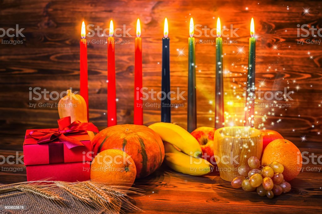 Kwanzaa holiday concept with traditional lit candles, gift box, pumpkins, ears of wheat and miracle magic light on wood background stock photo