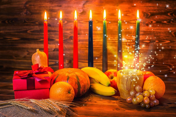 kwanzaa holiday concept with traditional lit candles, gift box, pumpkins, ears of wheat and miracle magic light on wood background - kwanzaa stock pictures, royalty-free photos & images