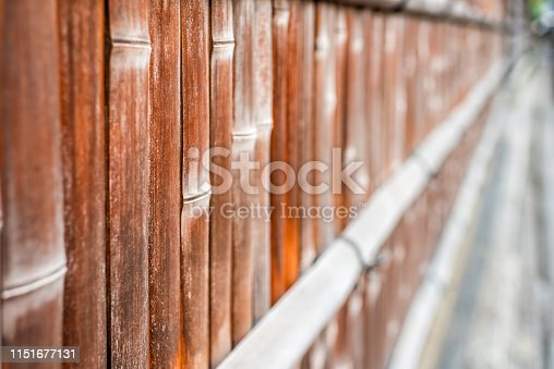 Kyoto, Japan residential area with closeup of bamboo wooden fence with red orange brown color by sidewalk