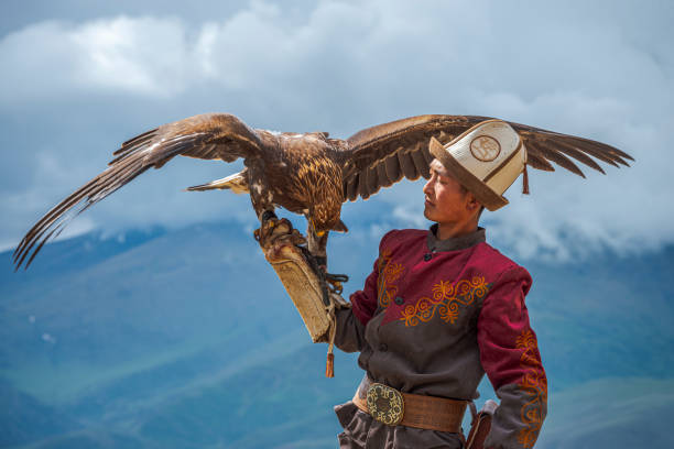 Kyrgyz Hunter  Eagle Traditional Kyrgyz Hunter Holding Eagle kazakhstan stock pictures, royalty-free photos & images