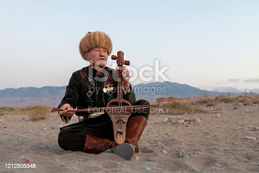 Issyk Kul, Kyrgyzstan, October 15, 2017: Kyrgyz musician playing traditional musical instrument known as Komuz, in Issyik Kul, Kyrgyzstan