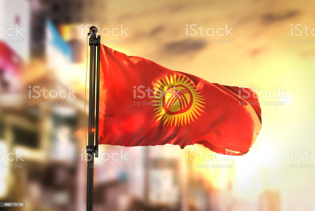 Kyrgyzstan Flag Against City Blurred Background At Sunrise Backlight stock photo