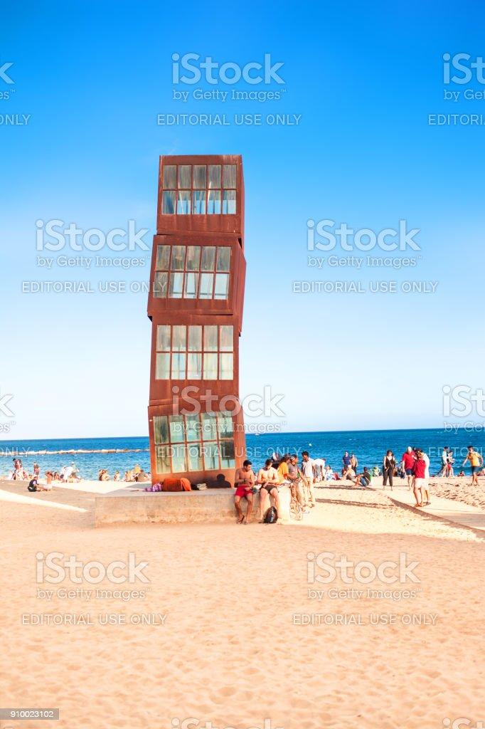 La playa de la Barceloneta con personas en el hermoso día soleado y monumento Homenatge a la Barceloneta por la artista Rebecca Horn, Barcelona, Cataluña, España - foto de stock