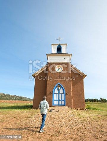 La Cueva (Mora County), NM: A man approaches San Rafael Church, built in the mid-1800s. La Cueva is about 30 miles north of Las Vegas, NM.