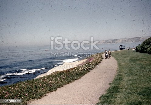 La Jolla, United States - January 01, 1965:  Two women are visible in the distance walking a baby carriage along the shoreline of the Pacific Ocean in La Jolla, California, 1965