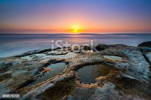 Beautiful sunset at La Jolla California with a starfish in a tide pool.