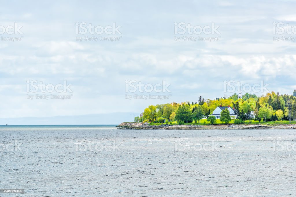 La Malbaie, Canada Saint Lawrence river town cityscape skyline in Charlevoix region in Quebec with church steeple, houses, rocks, rocky beach shore stock photo
