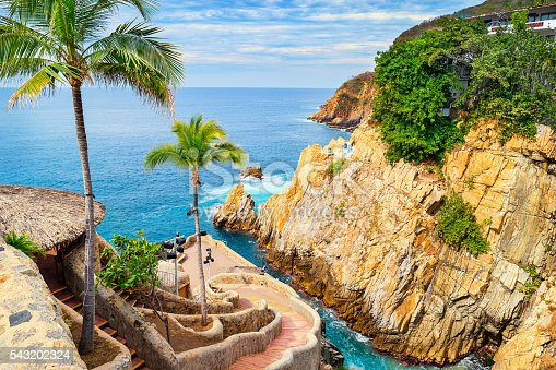 Photo of the landmark La Quebrada diving cliffs and waterfront promenade in Acapulco, Mexico.  La Quebrada is famous for the divers that entertain tourists by jumping off the cliff.