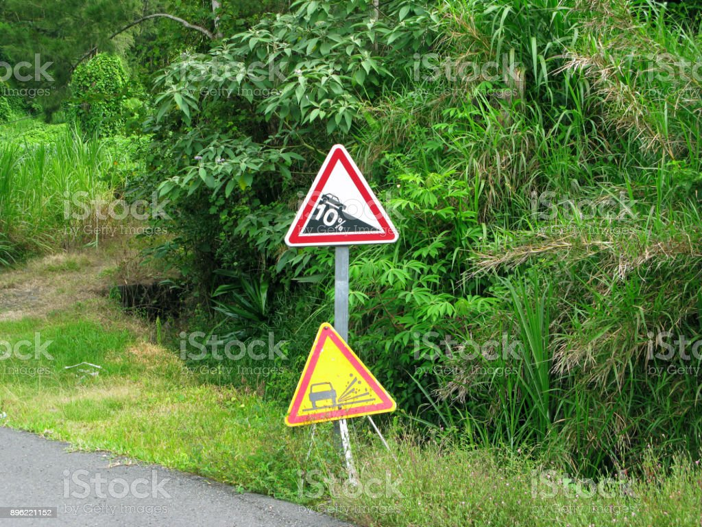 """La Reunion: """"10 % descent"""" warning sign and temporary warning sign """"loose gravel"""" stock photo"""