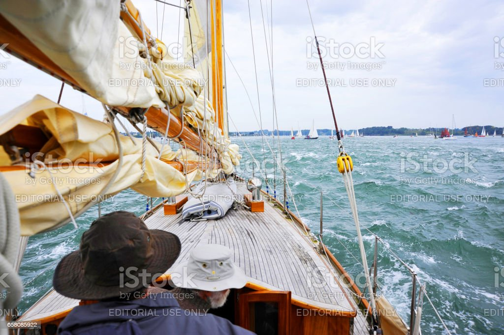 La Semaine du Golfe; bi-annual classic boat festival. View forward to mast, boat deck, sea, yachts and horizon; two crew in foreground. royalty-free stock photo