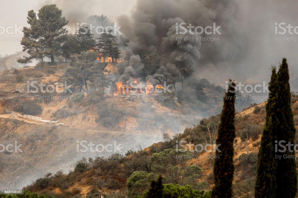 La Tuna wildfire in Los Angeles, CA burning a structure stock photo
