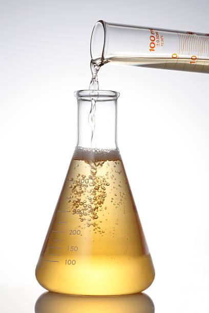 lab glaskolben und gießen flüssigkeit. - messzylinder stock-fotos und bilder