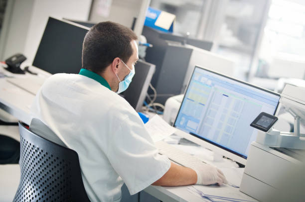 Lab technician entering data into computer. stock photo