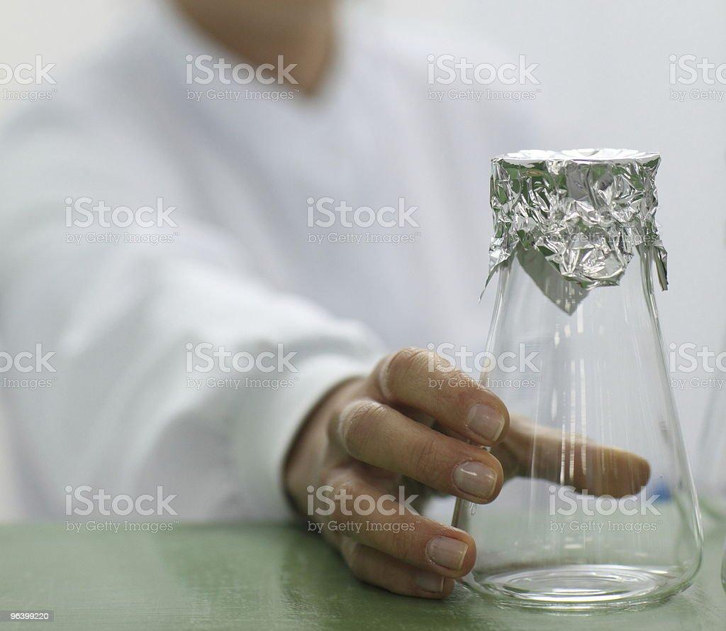 Lab technician holding a glass beaker - Royalty-free Aluminum Stock Photo