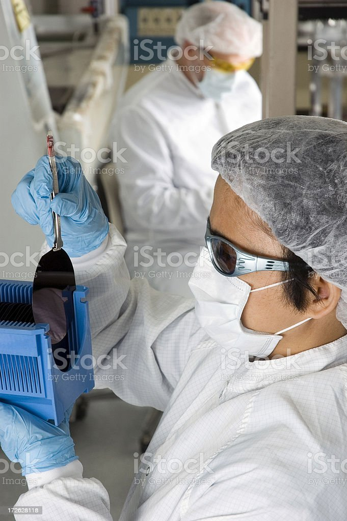 Lab Technician Inspecting a Silicon Wafer - Series stock photo