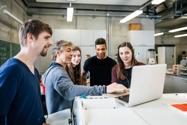 Laborantin im Gespräch mit Studenten vor Laptop – Foto