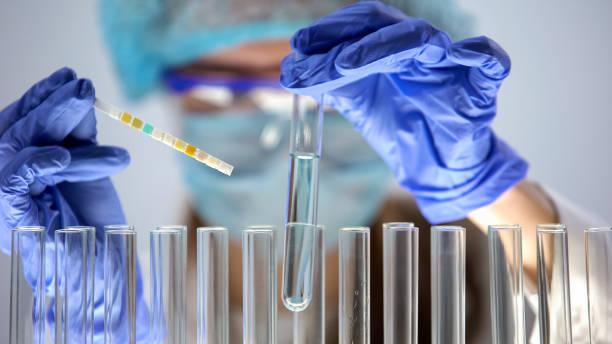 lab worker holding blue liquid tube measuring acidity level, scientific research - ricerca scientifica foto e immagini stock