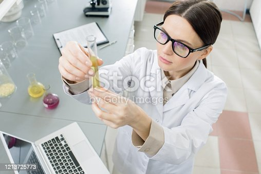 1147277006 istock photo Lab worker looking at flask with liquid substance while studying new vaccine 1213725773