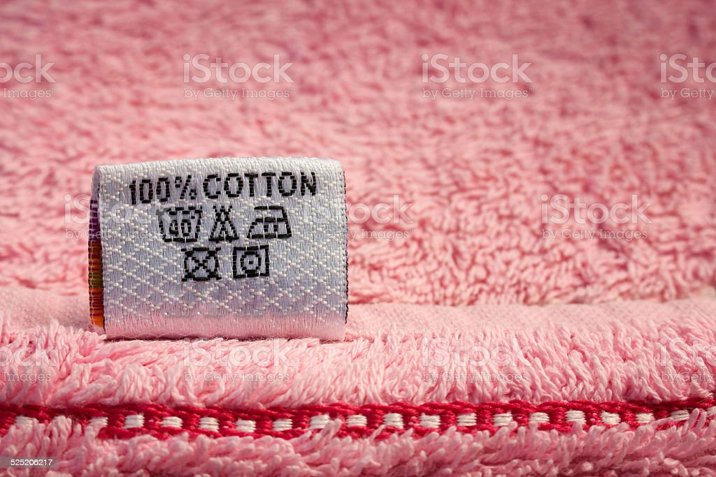 Label 100 % cotton on pink towel stock photo