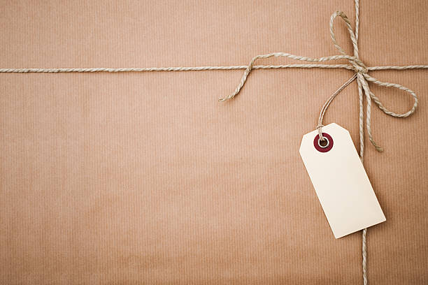label on a wrapped parcel - gift tag note stock photos and pictures