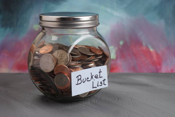 BUCKET LIST Label on Jar Filled with Coins stock photo