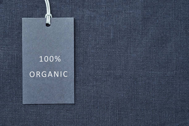Label on linen fabric background. 100% organic materal stock photo
