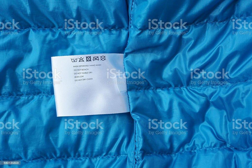 Label with washing instructions, on blue fabric background stock photo