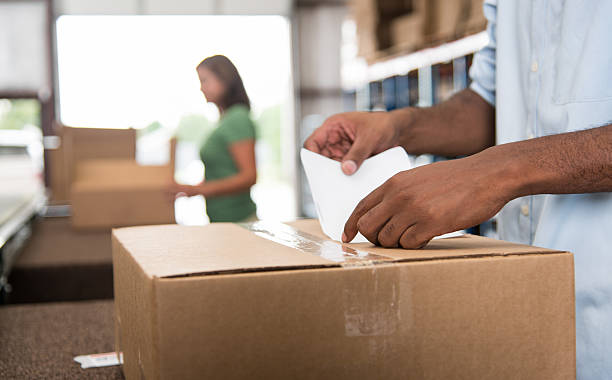 Labeling a box Filling orders in a warehouse labeling stock pictures, royalty-free photos & images