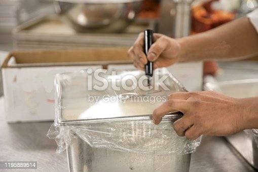 A rectangular metal food container is covered with clear wrap. An unrecognizable person is labeling the food with a permanent marker