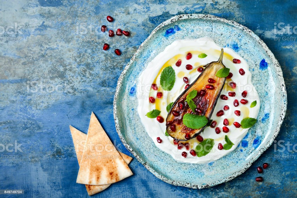 Labneh middle eastern lebanese cream cheese dip with roasted aubergine, pomegranate, mint and pita. Top view, overhead stock photo