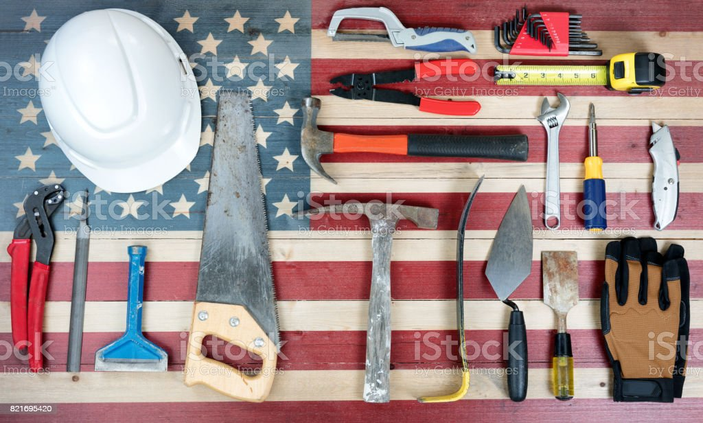 Labor Day holiday background with USA rustic wooden flag and many worker tools stock photo