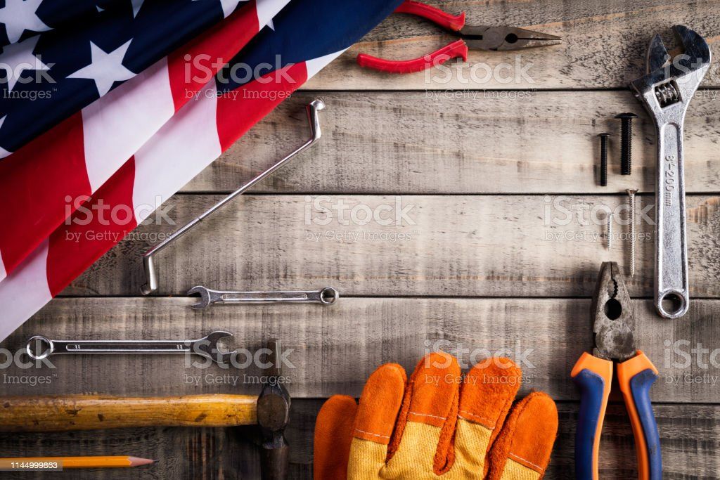 Labor Day, USA America flag with many handy tools on wooden...