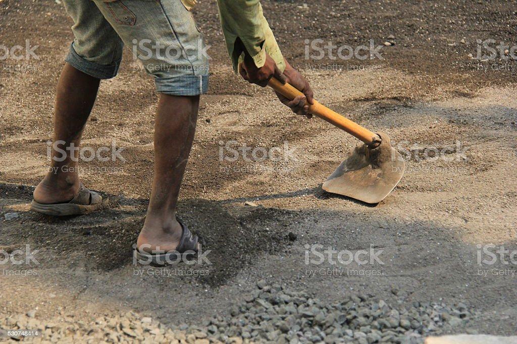 Labor shifting sand with shovel stock photo