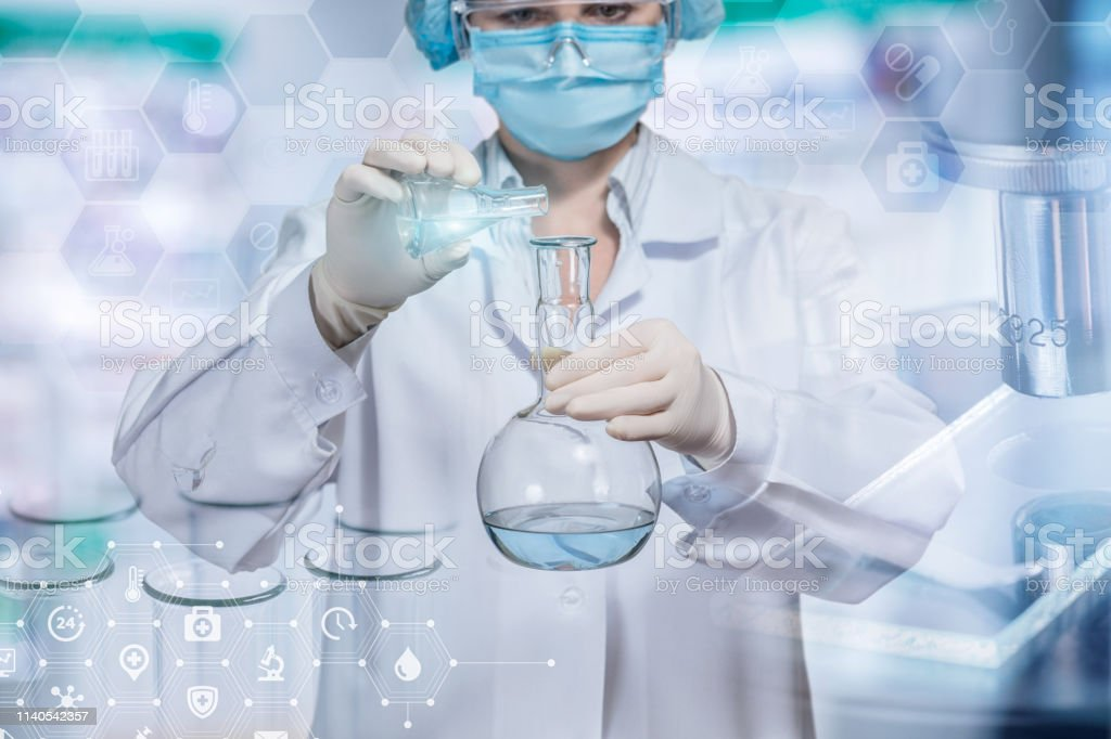 A laboratory assistant is pouring some liquid substance from tube...