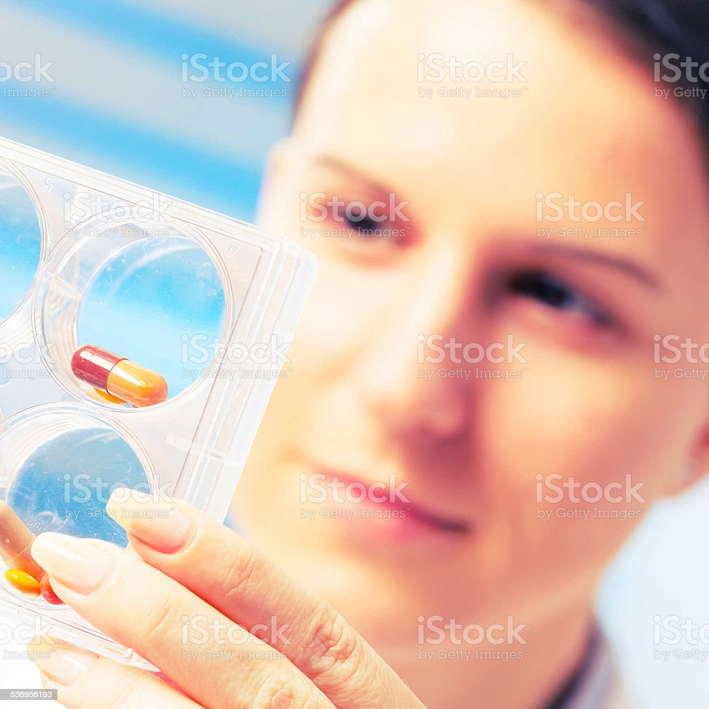 Laboratory assistant holds a  pills in  hand stock photo