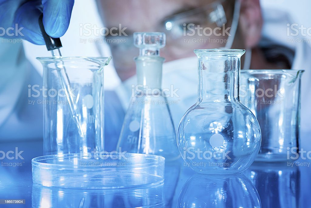 Laboratory Assistant or Researcher with Glass Beakers Flasks and Bottles stock photo
