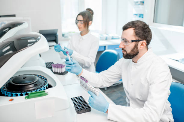 Laboratory assistants making analysis Laboratory assistants making analysis with test tubes and analyzer machines sitting at the modern laboratory medical sample stock pictures, royalty-free photos & images