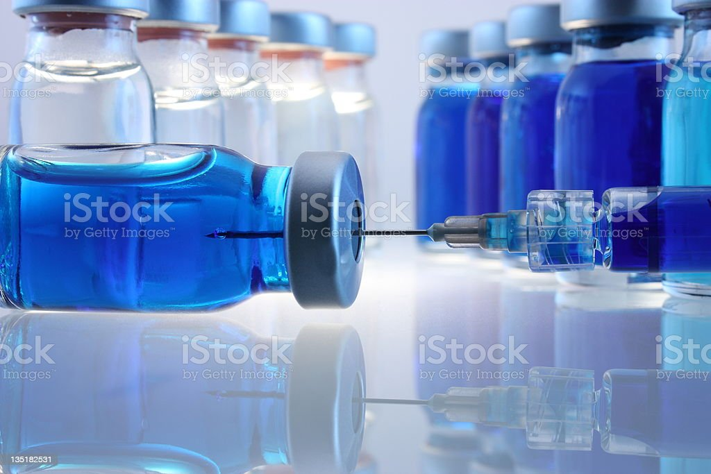 Laboratory bottles with blue content and a syringe stock photo