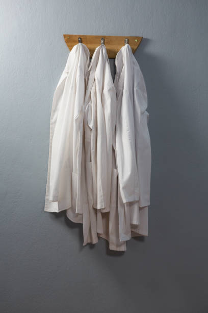 laboratory coat hanging on hook - laboratory coat stock photos and pictures