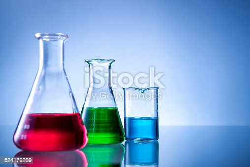 891126112istockphoto Laboratory equipment, bottles, flasks with color liquid  on blue background 524176269