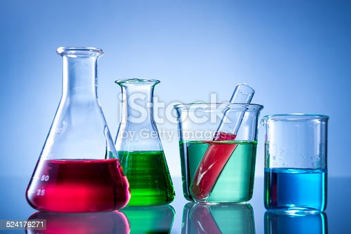 891126112istockphoto Laboratory equipment, bottles, flasks with color liquid  on blue background 524176271