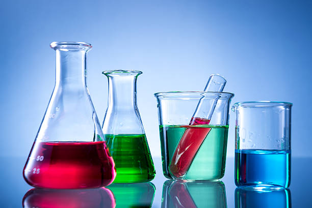 Laboratory equipment, bottles, flasks with color liquid  on blue background stock photo