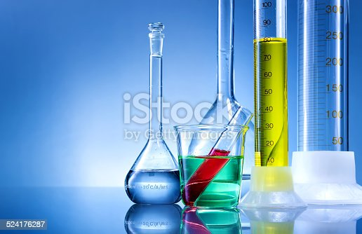 891126112istockphoto Laboratory equipment, bottles, flasks with color liquid  on blue background 524176287